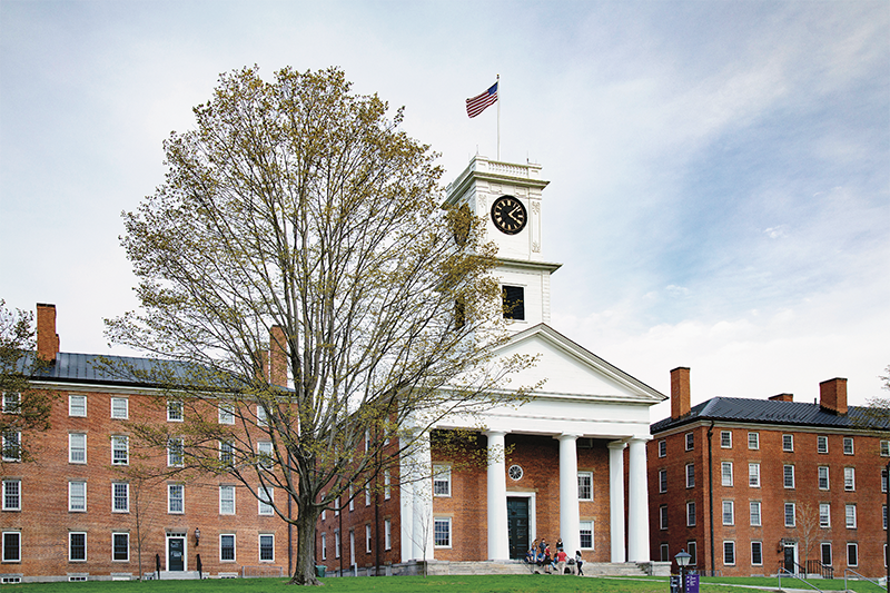 A bare tree in front of Johnson Chapel under a bright cloudy sky