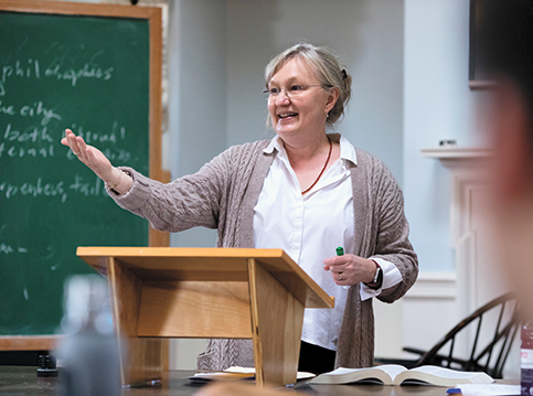 A woman speaking at a podium with a blackboard to the left