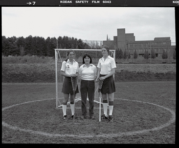 Katie Fretwell and two classmates in lacrosse uniforms standing in front of a goal post