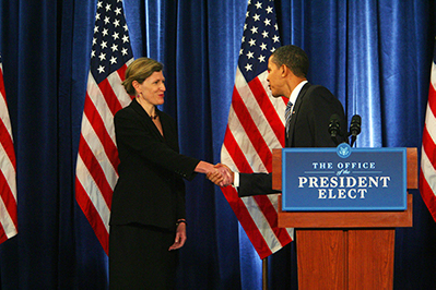A photo of Jeanne Lambrew shaking hands with President Obama in front of a series of American flags