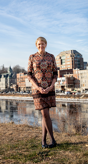 A woman in a colorful dress standing in front of a river with buildings and houses in the distance.