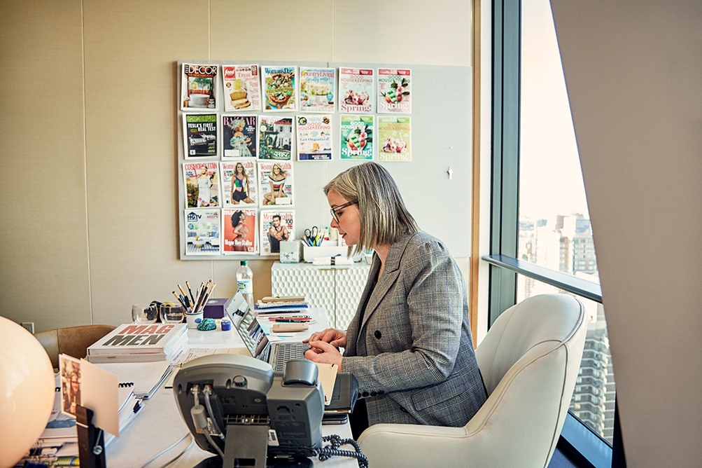 A woman at a desk kin a office with magazine covers on the wall.