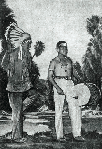 A black and white movie still of two people dressed as stereotypical Native Americans