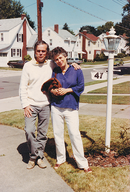 A man and woman poising for a photo in a suburban neighborhood