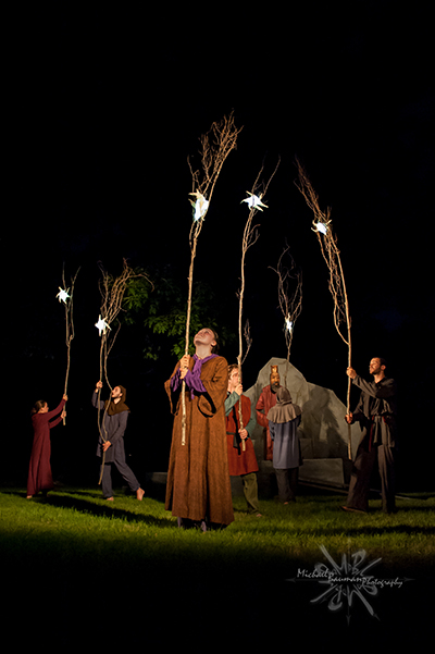 Actors hold branches with figures of moon and stars against the night sky