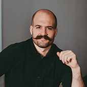 A man with a mustache poising for a photo