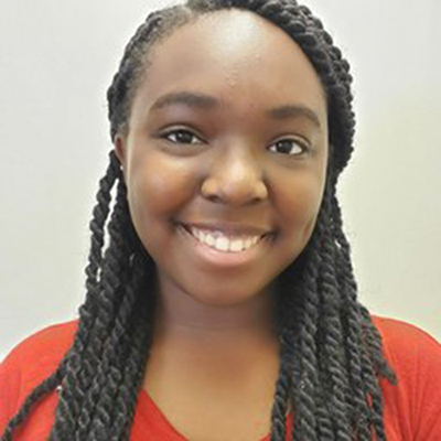 A young Black woman smiling at the camera