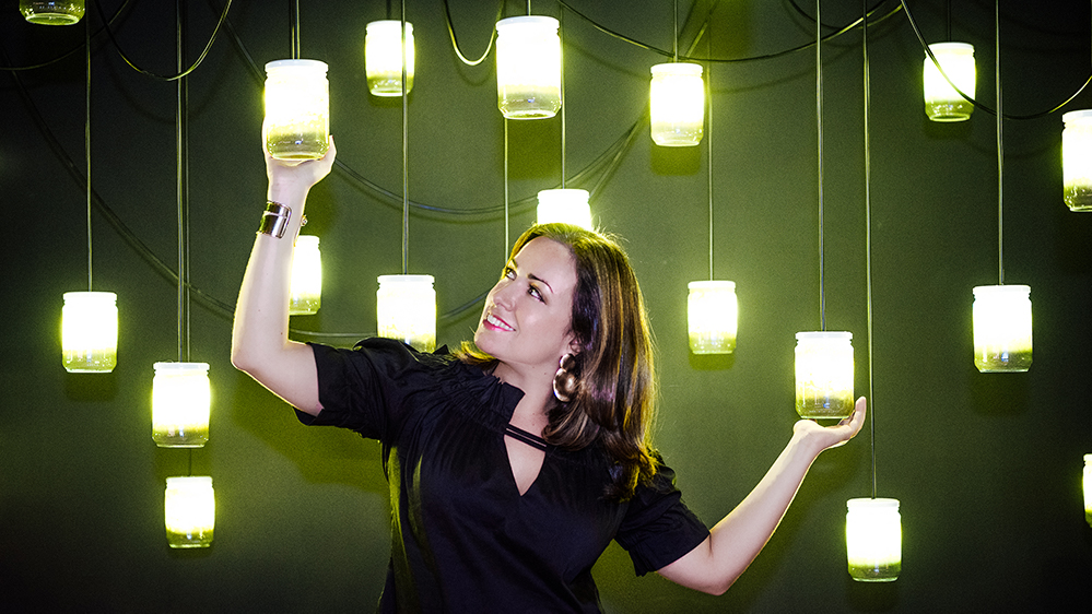 A woman with her hands raised holding large hanging lights
