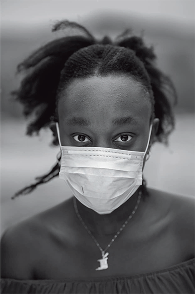 A young Black woman in a mask staring intently at the camera