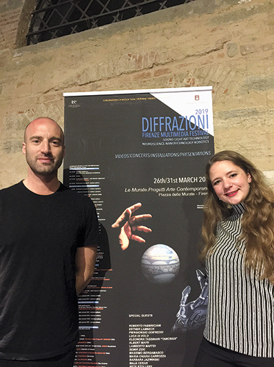 A man and woman standing in front of a poster saying Diffrazioni
