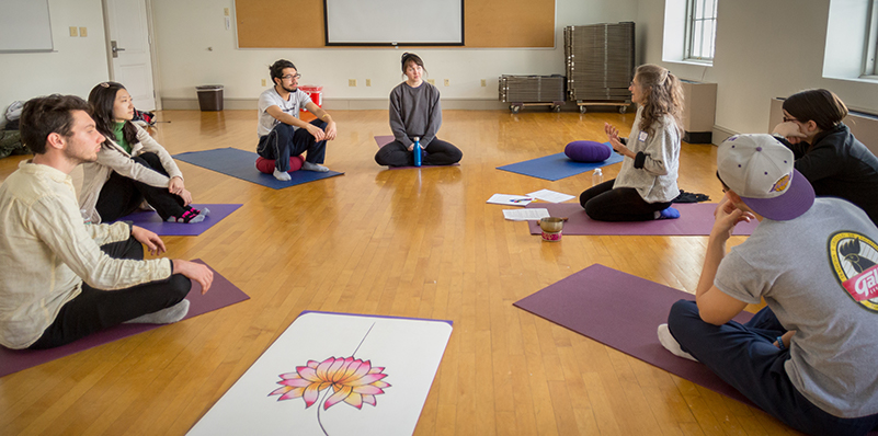 A group of students sitting in a semi-circle on yoga mats