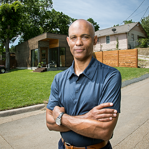 A Black man with his arms folded standing in front of a modern house