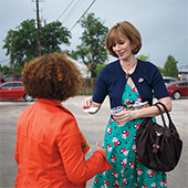 A woman handing a card to a woman in an orange jacket