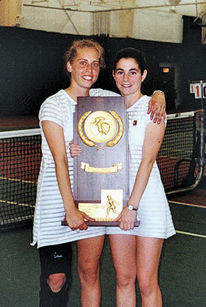 Two women tennis players holding a trophy