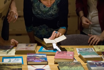 Three visitors bend over a table of books