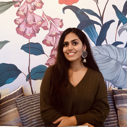 Omisha sitting in front of a floral mural.