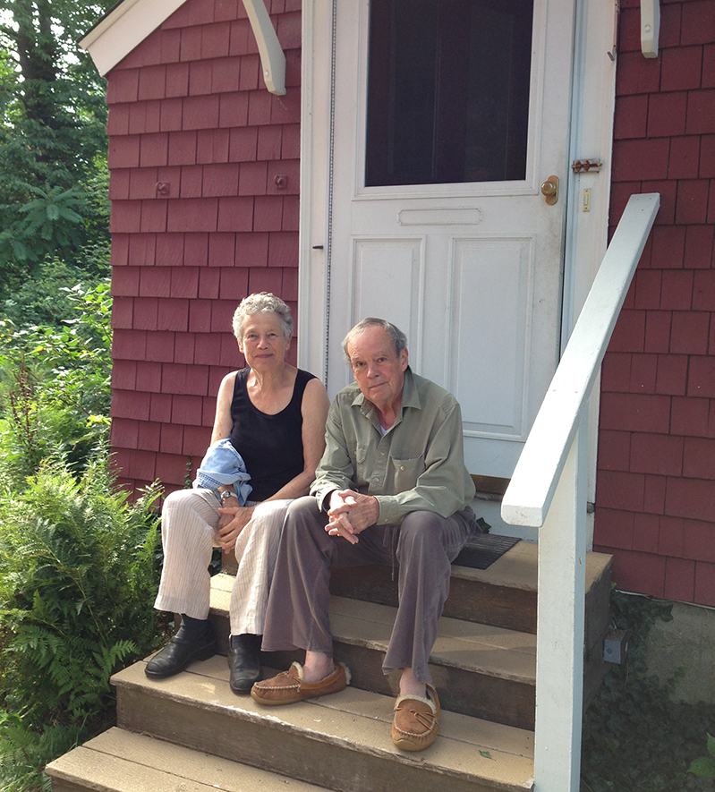 A man and woman on the back steps of a home