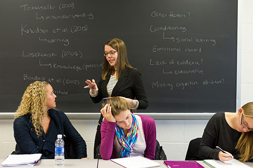 Carrie Palmquist in front of a blackboard, with three seated students