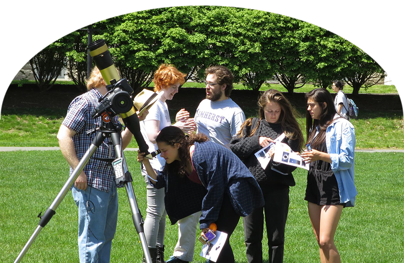Students gathered outside around a telescope.