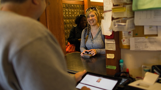 A young woman smiling at a post office counter