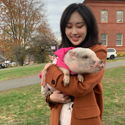 Qingfang holding a small pig on a campus quad