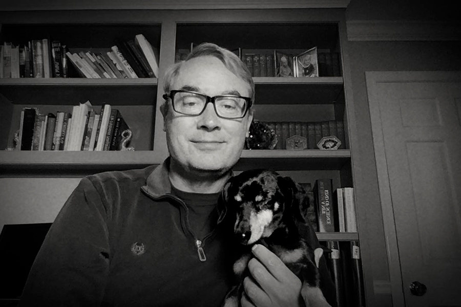 A black and white photo of an older man with glasses holding a dog