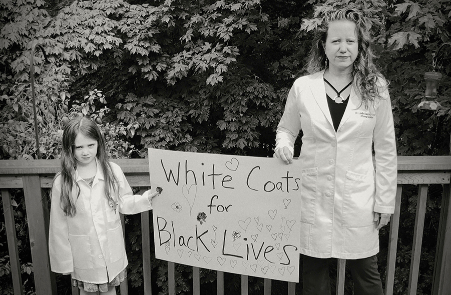"""A woman in a doctor's coat and a young child holding a sign that reads """"White Coats for Black Lives"""""""