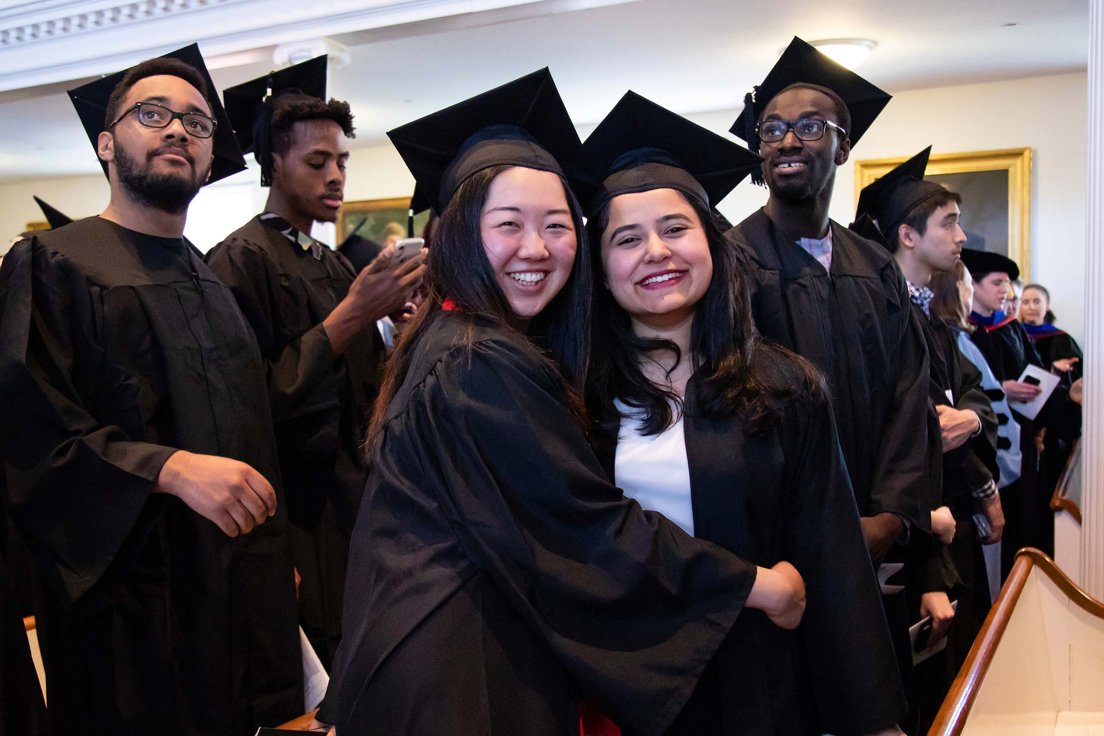 Smiling students wearing graduation gowns