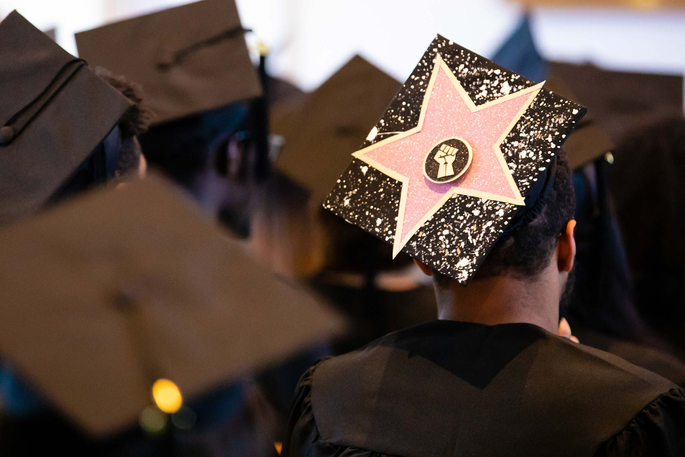 A close-up of a graduation cap decorated with a large pink star and a silhouette of a fisted hand