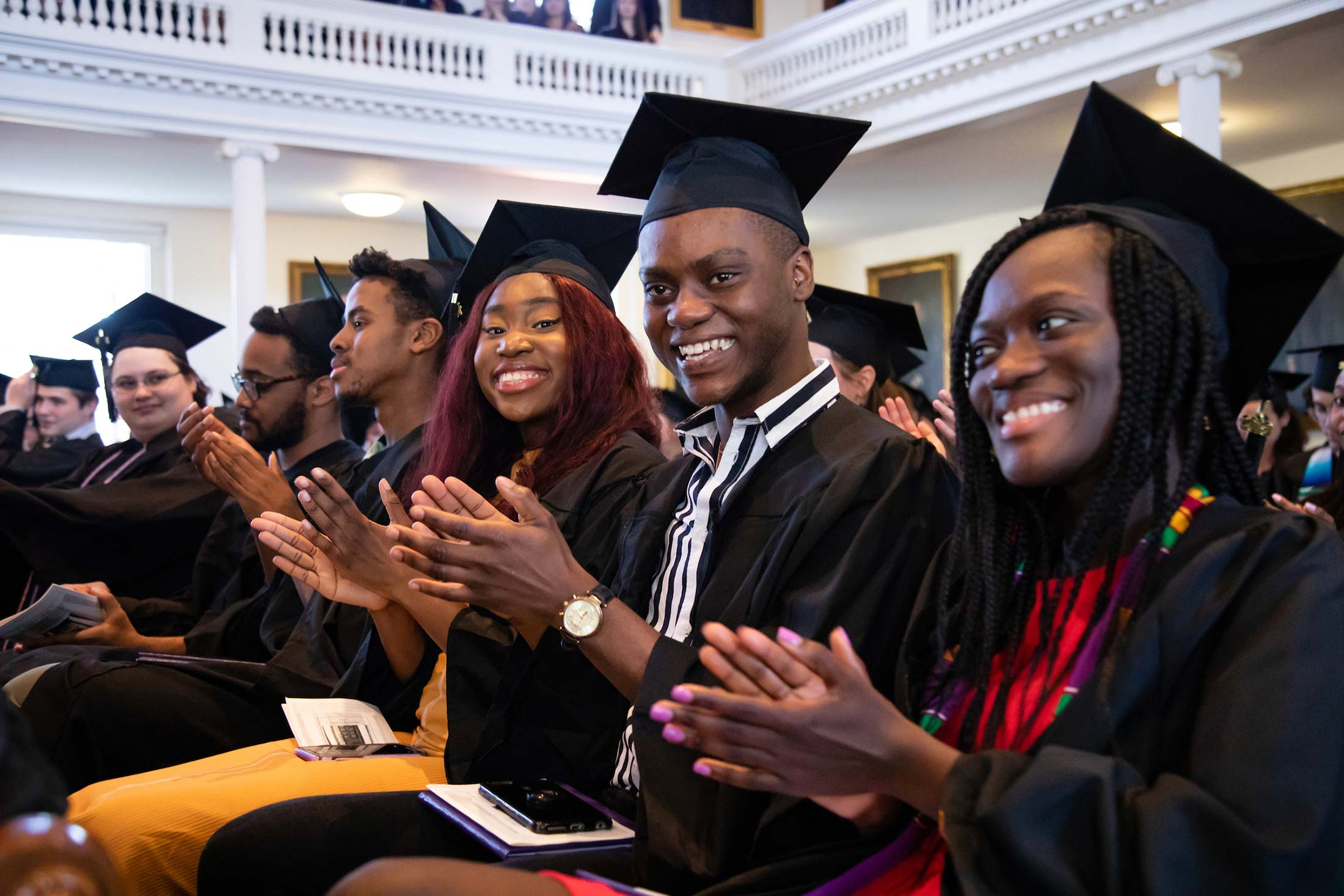 Student clapping during Senior Awards Assembly in Johnson Chapel at Amherst College