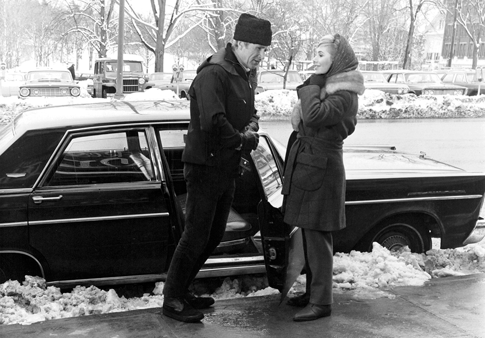 A black and white movie still of a man and woman standing next to a car with the door open