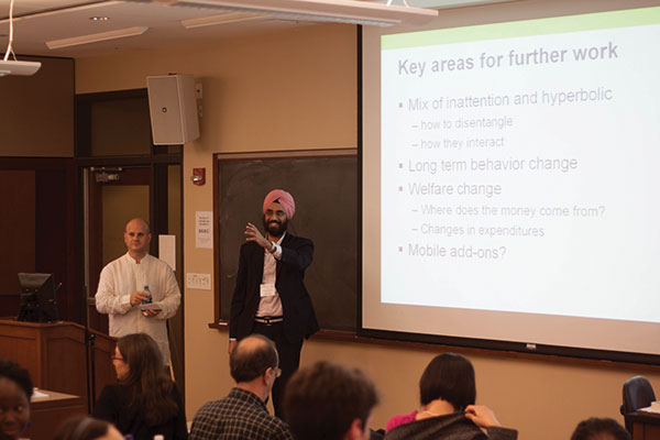 Singh giving a PowerPoint presentation in front of an audience