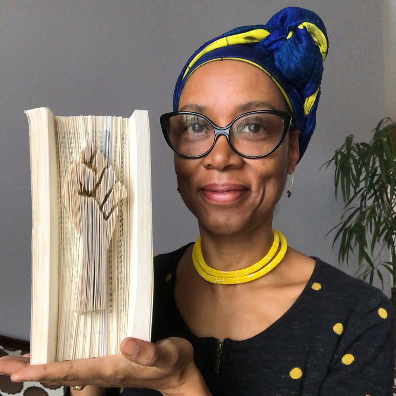 Sonya Clark holds a book containing a raised solidarity fist sculpted into its fore edge