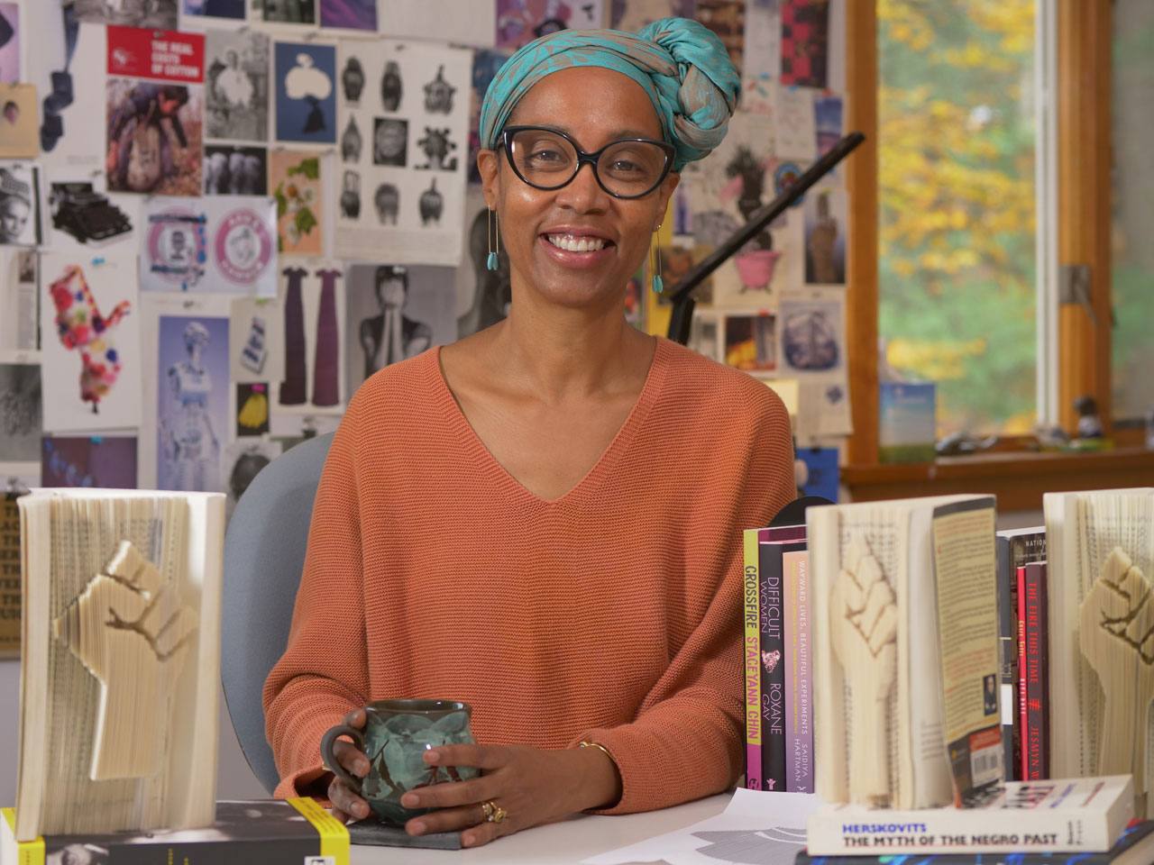 Sonya Clark sits in her art studio with sculpted books next to her