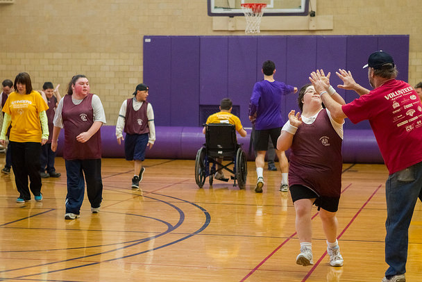 Special Olympics athletes, a coach and an Amherst College student on a basketball court in Alumni Gymnasium