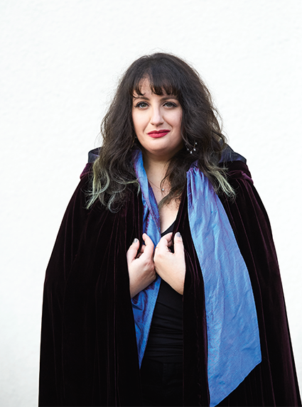 A portrait of woman in a black coat with a blue scarf
