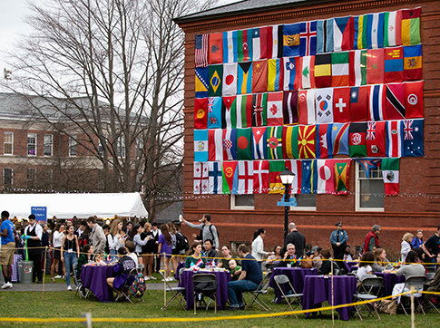 Students eating at tables outside under a wall of world flags