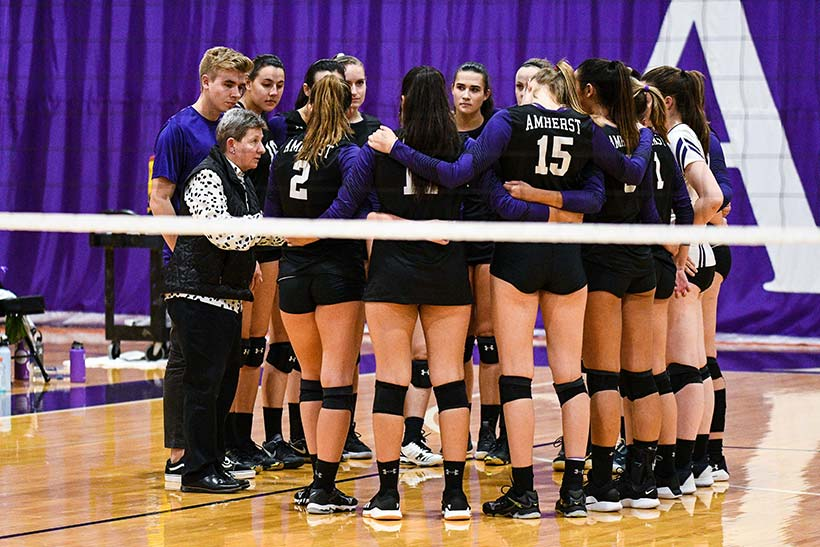 Sue Everden in a huddle with the volleyball team