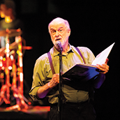 An older man on stage reading from a large book
