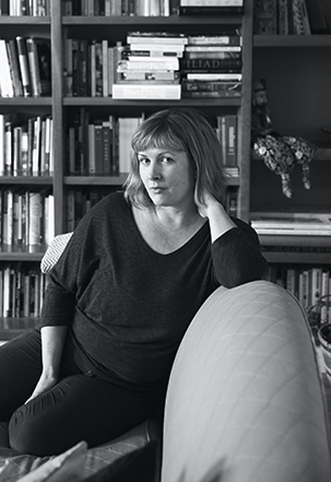 A black and white photo of a woman sitting on a couch