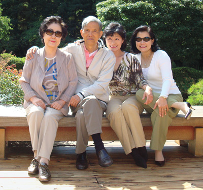 Thai Lee '80 sitting on bench in her garden, surrounded by sister and father and mother