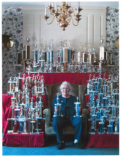 Barbara Tiffany surrounded by trophies