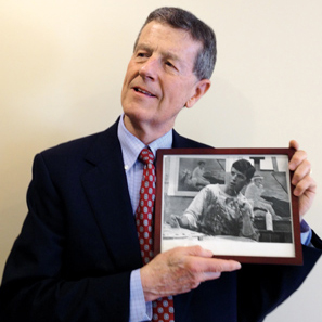 Bob Forrester'67 holding photo of of himself as art student.