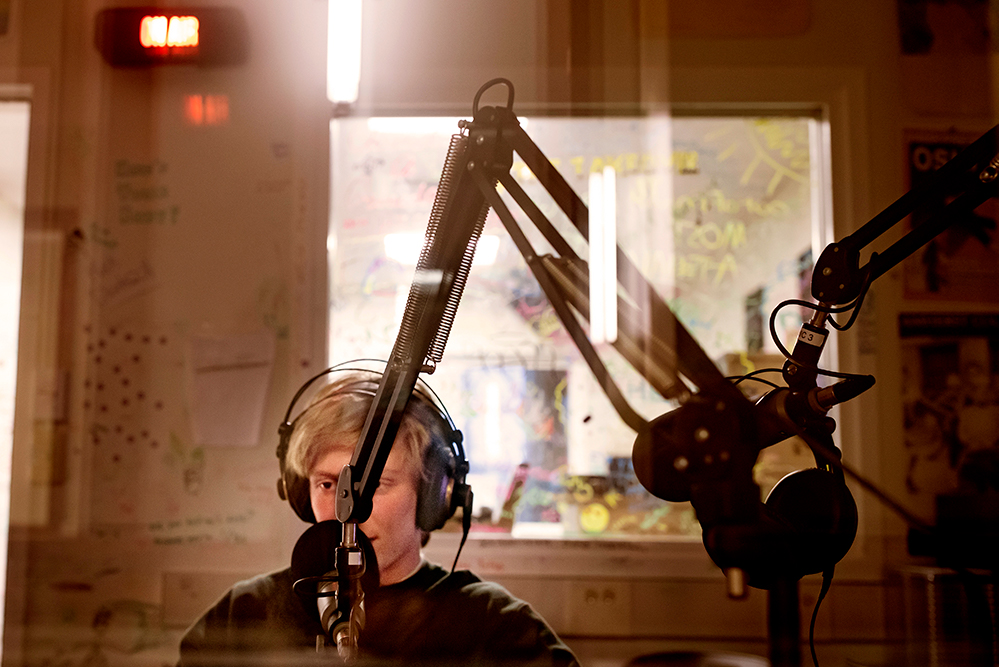 A young man in a radio studio speaking into a large microphone