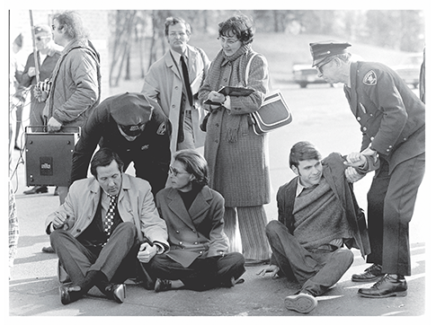 A black and white photo of two men and a woman sitting in protest and getting arrested