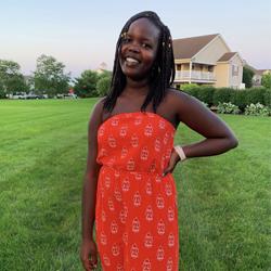 Yvette posing in front of a green lawn.