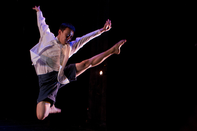 A student dancer leaps into the air in a performance