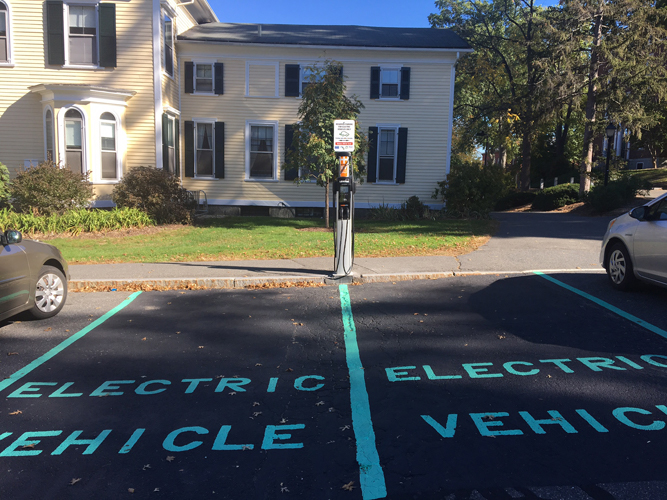 Two parking spaces marked Electric Vehicle, next to an electric charger