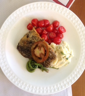 Plate of fish, cherry tomatoes, potatoes