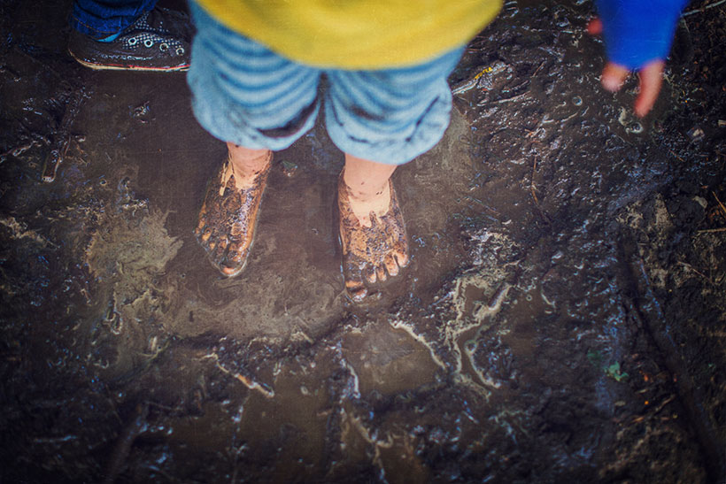 A kids standing with their feet in the mud
